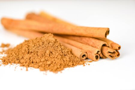 Cinnamon sticks and cinnamon powder herbs and spices on white background