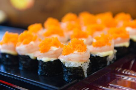 Japanese food shrimp sushi roll rice with tobiko egg is orange (flying fish roe) nori in the restaurant sushi menu set japanese cuisine fresh ingredients on tray , selective focus