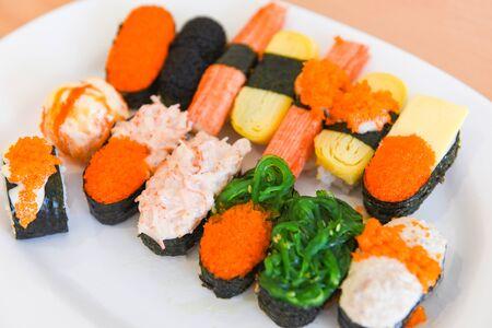 Japanese food sushi roll rice with tobiko egg red caviar cream sauce nori seaweed in the restaurant sashimi sushi menu set Japanese cuisine fresh ingredients mix various types on white plate