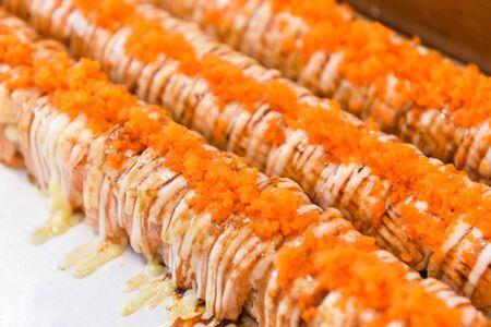 Salmon sashimi japanese food sushi  with Tobiko egg cream sauce on salmon fillet in the restaurant  Sashimi sushi menu set Japanese cuisine fresh ingredients on tray , top view selective focus