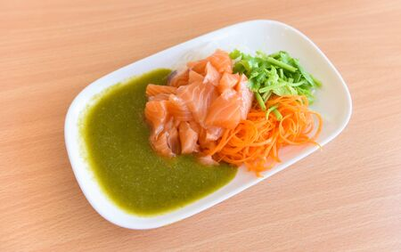 Japanese food raw sashimi salmon fillet with carrot celery seafood sauce in the restaurant  salmon salad menu set Japanese cuisine fresh ingredients on plate , selective focus