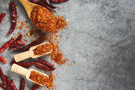 cayenne pepper on wooden spoon spices and dried chilli peppers background  group of red hot chilli powder on black plate top view ingredients table asian food spicy in thailand