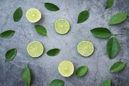 Flat lay top view lime slices with lime leaf on dark background  Banco de Imagens