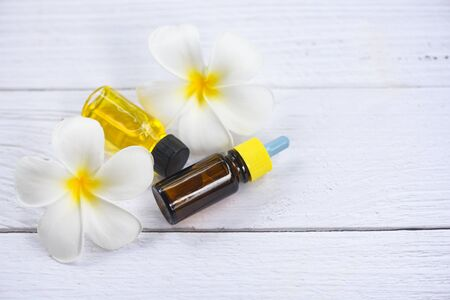 Aromatherapy herbal oil bottles aroma with white flower Frangipani Plumeriaon top view  Essential oils natural on wooden table and organic minimalist Banco de Imagens