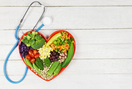 Healthy food selection clean eating for heart life cholesterol diet health concept. Fresh salad fruit and green vegetables mixed various beans nuts grain on red heart plate for healthy food vegan cook