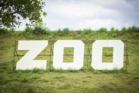 White sign of zoo on field slope hill / The Zoo Stockfoto
