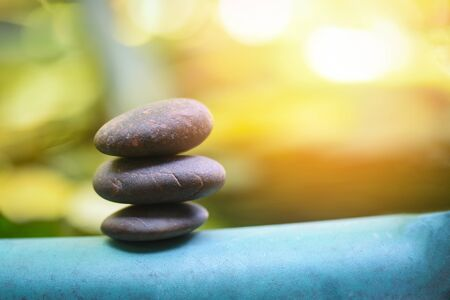 Natural wellness concept  Relax zen stones stack on wooden nature green background Spa Natural Alternative Therapy With Massage Stones