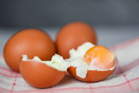 boiled egg on glass bowl and fresh eggs on the table background top view / Soft boiled eggs