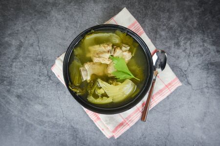 Pickled lettuce soup with spare ribs pork bone soup bowl with vegetable on table Banco de Imagens