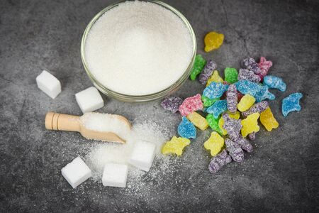 White sugar and colorful candy sweet on the dark table background  No sugar in diet causes obesity diabetes and other health problems concept , selective focus Stok Fotoğraf