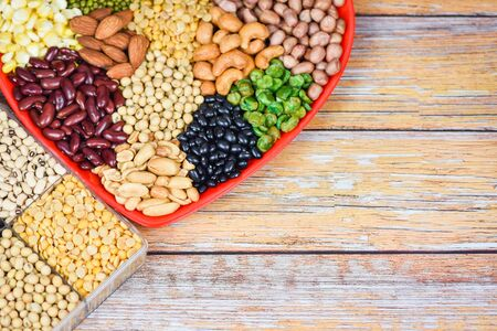Collage various beans mix peas agriculture of natural healthy food for cooking ingredients  Set of different whole grains beans and legumes seeds lentils and nuts colorful on red heart background