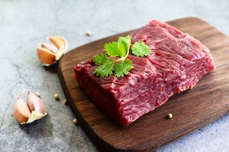 Fresh beef piece for steak or grilled barbecue, Raw meat beef steak with spices garlic on wooden cutting board and black background, top view Stock Photo