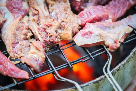 Roast beef sliced meat steaks on the grill with flames Grilled beef barbecue at street food Thailand Asian