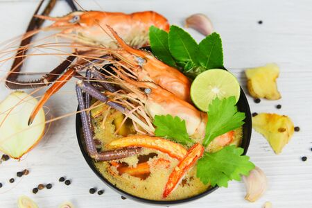 Tom Yum Kung thai food asian traditional Prawn spicy soup bowl cooked seafood with shrimp soup dinner table and spices ingredients Stock Photo
