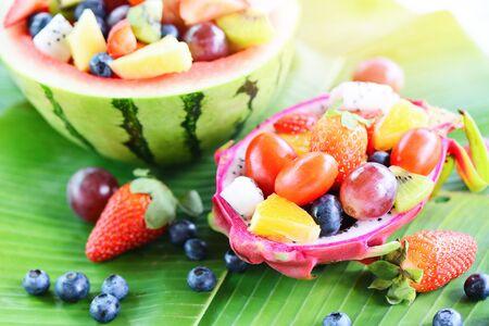 Sałatka owocowa podana w smoku owoce i arbuz warzywa zdrowe jedzenie truskawki pomarańcza kiwi jagody winogrona ananas pomidor cytryna świeże letnie owoce tropikalne na liściu bananowca
