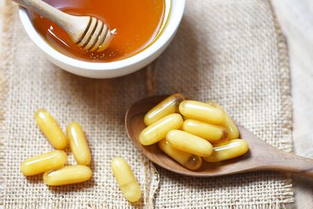 Royal jelly capsules in wooden spoon on sack background and honey in cup / Yellow capsule medicine or supplementary food from nature for health Stock Photo