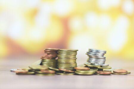 Monedas en la mesa / Pila de monedas de oro, monedas de plata y monedas de cobre en concepto financiero de dinero de madera Foto de archivo