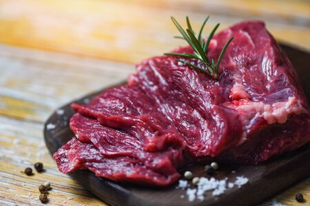 Raw beef steak with herb and spices / Fresh meat beef sliced on wooden cutting board background Stock Photo