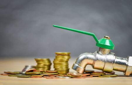 faucet on money coin wood background  water savings and faucet money fall concept