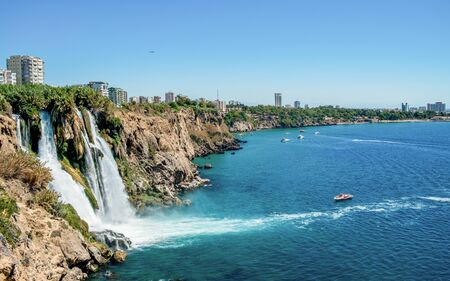 Waterfall Duden at Antalya turkey top view on the mountain with coast ferry boat on blue sea and harbor city background  Beautiful antalya beach Turkey landscape travel landmark