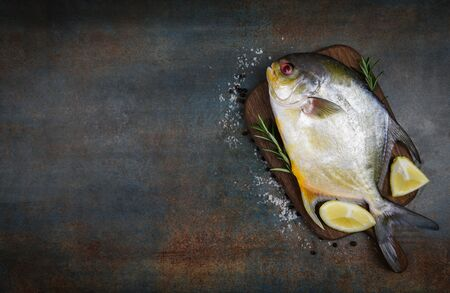 Fresh pomfret fish with herbs spices rosemary and lemon on wooden cutting board and black plate background  Raw black pomfret fish