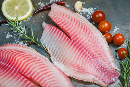 Fresh fish fillet sliced for steak or salad with herbs spices rosemary tomato and lemon  Raw tilapia fillet fish on plate and ingredients for cooking food Stok Fotoğraf