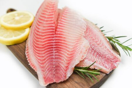 Fresh fish fillet sliced for steak or salad with herbs spices rosemary and lemon  Raw tilapia fillet fish on wooden cutting board and white background and ingredients for cooking food  Stok Fotoğraf