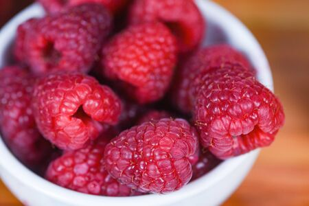 Fresh raspberry on bowl  Close up red raspberries fruit on wood background , top view