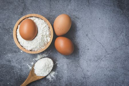 Homemade flour eggs cooking ingredients on kitchen table  Pastry flour on wooden bowl on gray background , top view