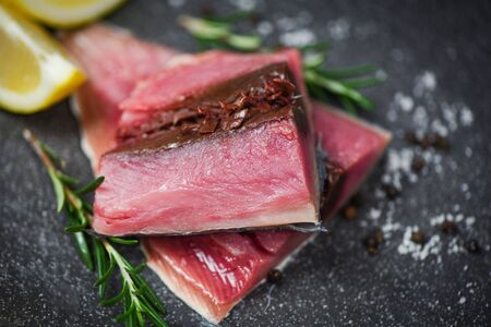 Fresh fish fillet sliced for steak or salad with herbs spices rosemary and lemon  Raw fish seafood on black plate background , Longtail tuna , Eastern little tuna fillet ingredients for cooking food