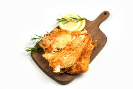 fried fish fillet sliced for steak or salad cooking food with herbs spices rosemary and lemon  tilapia fillet fish crispy served on wooden cutting board and white background