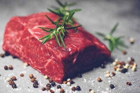 Fresh meat beef sliced on black background  Raw beef steak with herb and spices and rosemary on plate  Stok Fotoğraf