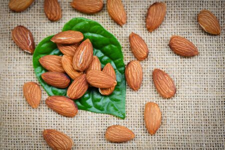 Almonds on sack background with green leaf  Close up almond nuts natural protein food and for snack Stok Fotoğraf