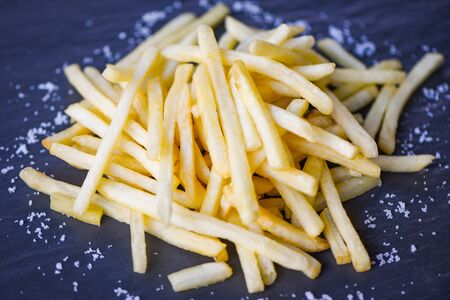 Fresh french fries with salt on black plate  Tasty potato fries for food or snack delicious Italian meny homemade ingredients