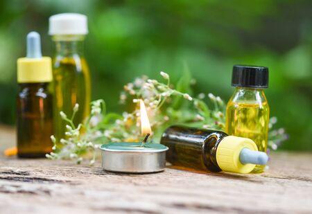 Aromathérapie bouteilles d'huile à base de plantes arôme avec feuilles de fleurs formulations à base de plantes comprenant des fleurs sauvages et des herbes sur bois / Bougies parfumées huiles essentielles naturelles sur fond de bois et de feuilles vertes