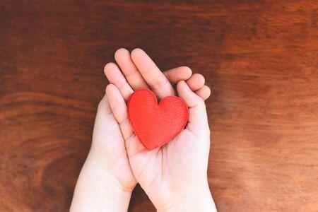 Herz in der Hand für Philanthropie-Konzept / Frau, die zum Valentinstag rotes Herz an den Händen hält oder spendet, um Liebeswärme zu geben, mit Holzhintergrund aufzupassen