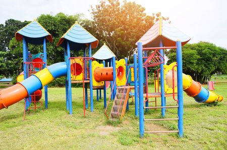 Children playground on outdoors activities in the garden with green trees background / Colorful playground on yard in the park