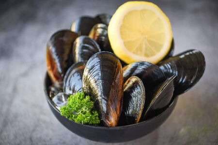 Raw Mussels with herbs lemon on bowl and dark background  Fresh seafood shellfish on ice in the restaurant or for sale in the market mussel shell food