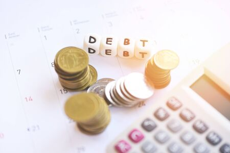 Calculator and coin stack on calendar with debt payday at the office financial counting / debt management concept