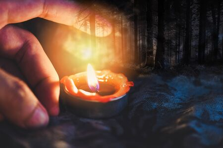 Hand with candlelight burning candle on the darkness scary forest background for Astrology Occult Magic illustration / Magic Spiritual Horoscopes and Palm reading fortune teller concept