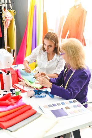 Fashion designer studio measuring textile material scissors cutting fabric by senior woman designer stylish showroom hanging clothes sewing machine and crafting tools designer working professional