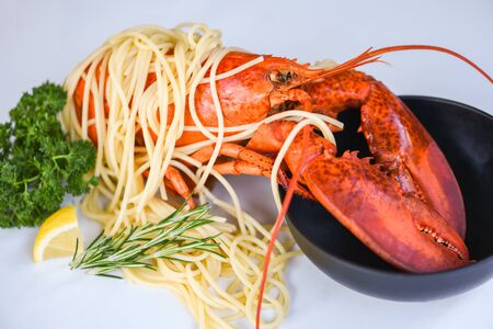 Spaghetti seafood lobster food on a white plate with herb spices lemon rosemary served table in the restaurant gourmet food healthy boiled lobster cooked salad spaghetti shrimp on bowl