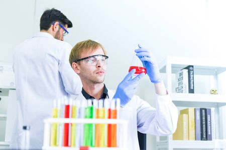 Man doctor as male scientist team doing some research working conduct experiments in modern laboratory / Scientists in lab biochemistry genetics forensics microbiology and test tube