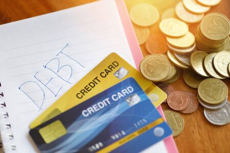 Debt credit card with calculator and coin stack on notebook paper in the office financial counting / debt management concept