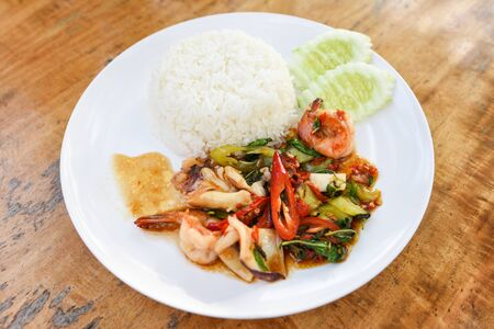 Stir fried seafood squid shrimp prawn with holy basil and rice / Thai food spicy fried recipe with cucumber and chili