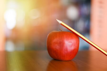pencil on a apple on the table in the library  Education learning on wood desk and blurred bookshelf room background