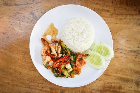 Stir fried seafood squid shrimp prawn with holy basil and rice / Thai food spicy fried recipe with cucumber and chili , top view  Foto de archivo