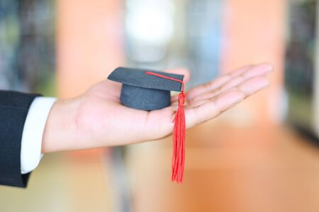 Graduation Education Business Study Concept / Business man or student with graduation cap on hand in day graduation congratulated the graduates in University