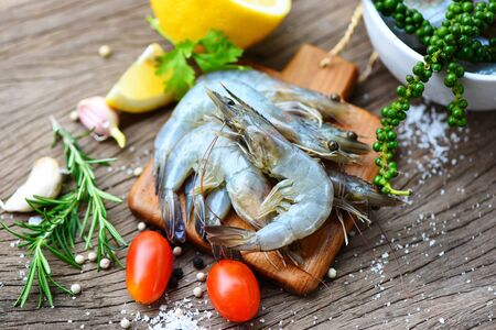 fresh shrimp on wooden cutting board with ingredients herb and spices for cooking seafood / raw shrimps prawns