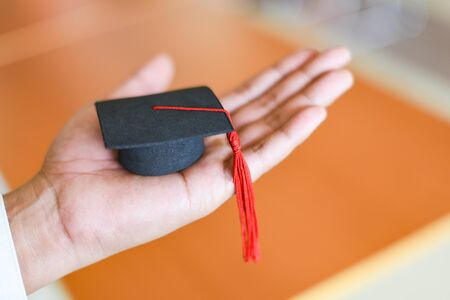 Graduation Education Business Study Concept / Business man or student with graduation cap on hand in day graduation congratulated the graduates in library at University
